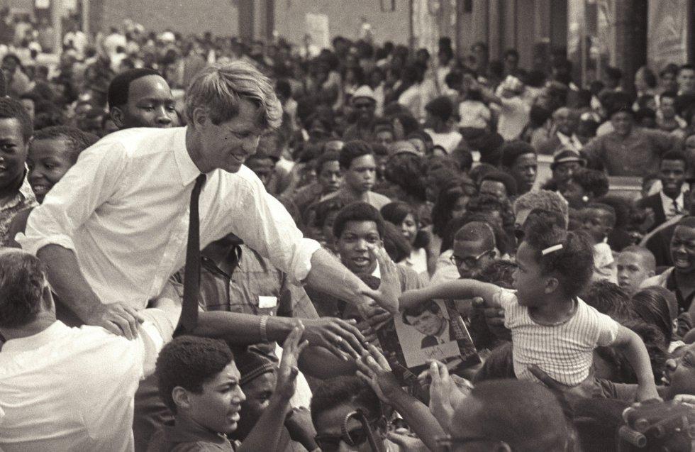 El senador Robert F. Kennedy saluda desde un descapotable a sus seguidores durante un mitin en Detroit