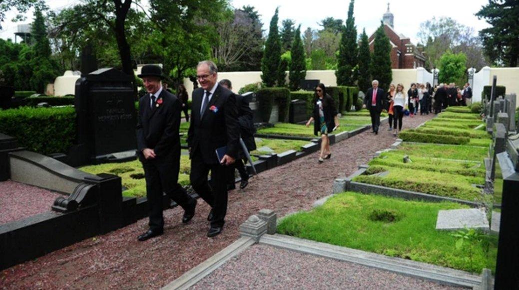 Los embajadores del Reino Unido y Alemania caminan por el cementerio alemán.