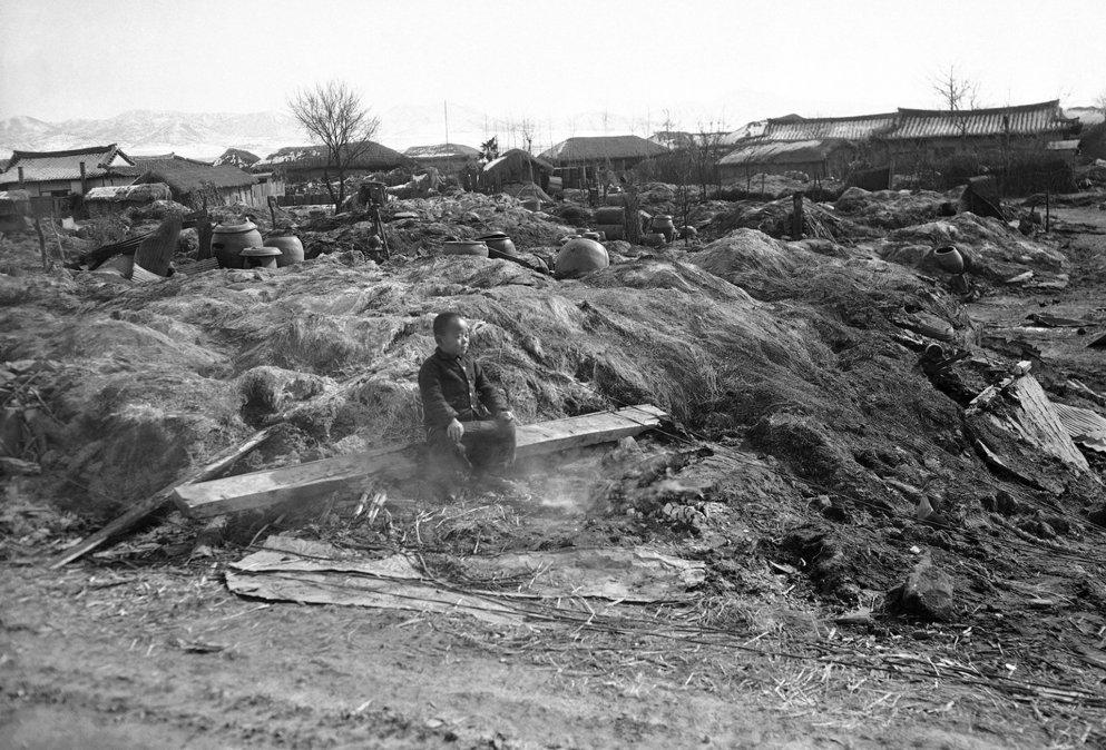Un niño sentado en las humeantes ruinas de su casa destruida por el fuego.