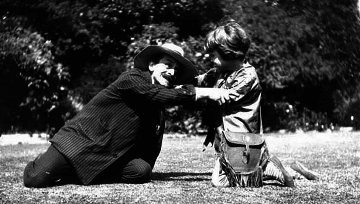 J.M. Barrie como elcapitán Garfiocon Michael Llewelyn Davies como Peter Pan jugando en los Jardines de Kensington.