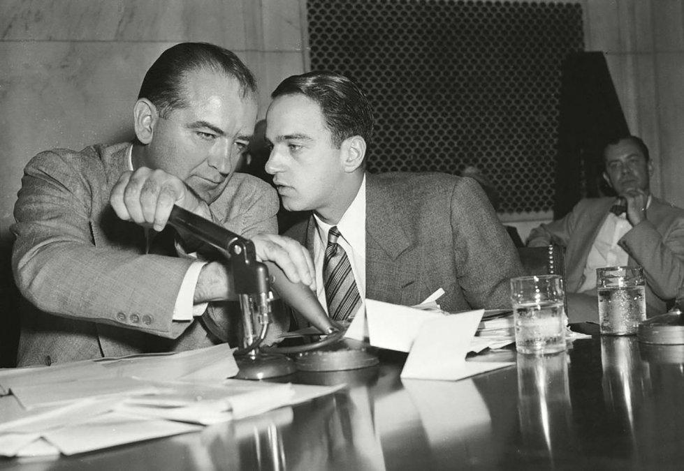 El senador Joseph McCarthy tapa el micrófono para consultar a su  asesor legal